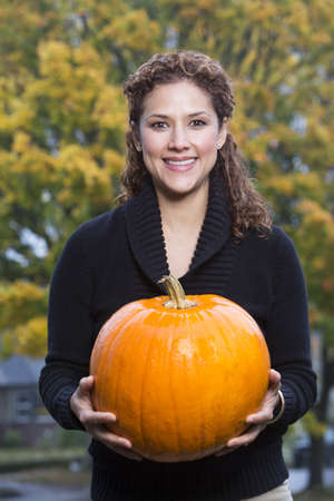 Hispanic woman holding pumpkin outdoors LANG_EVOIMAGES