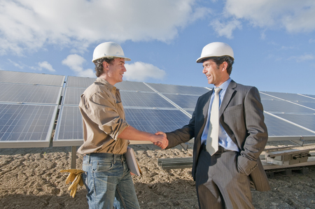 Businessman shaking engineers hand in solar plant