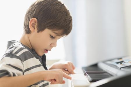 Hispanic boy practicing piano LANG_EVOIMAGES