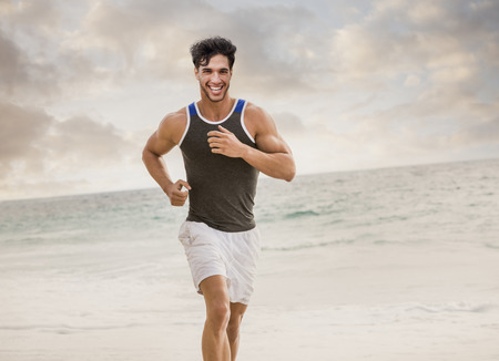 Caucasian man running on beach LANG_EVOIMAGES