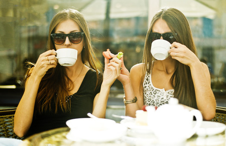Women having coffee together at sidewalk cafe