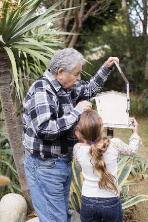 Senior Caucasian man and granddaughter checking mailbox
