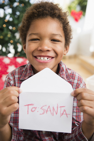 Black boy holding letter to Santa Claus