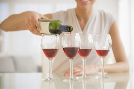 Black woman pouring glasses of wine