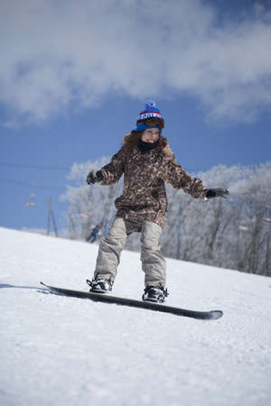 Asian woman snowboarding on snowy slope LANG_EVOIMAGES
