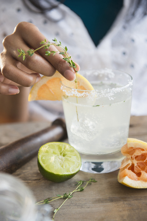 Mixed race woman making cocktail
