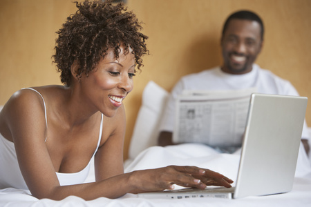 African American woman using laptop on bed
