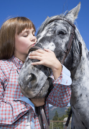 Mixed race girl kissing horse on ranch