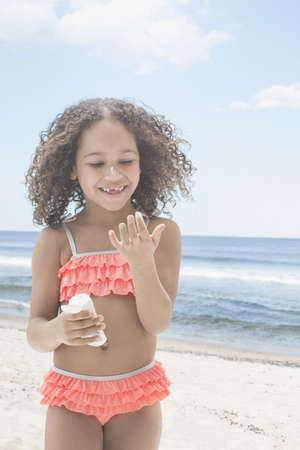 Mixed race girl applying sunscreen on beach