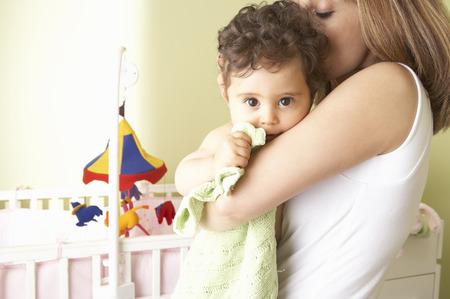 Middle Eastern woman cradling baby in nursery