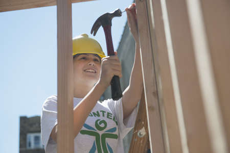 Caucasian volunteer building house