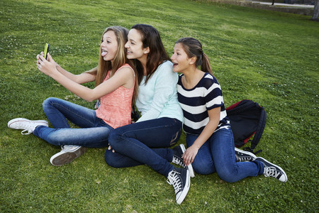 Teenage girls taking pictures in grass