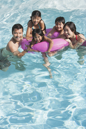 Family playing together in swimming pool