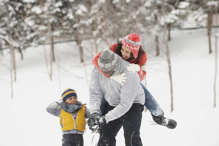 Black family playing in snow LANG_EVOIMAGES