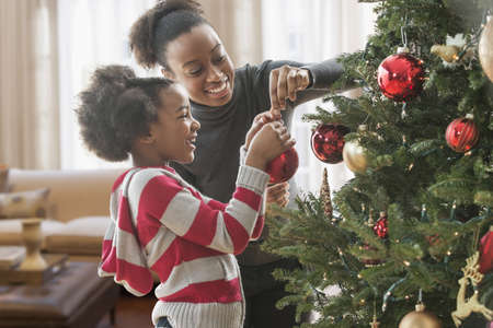 Mother and daughter decorating Christmas tree LANG_EVOIMAGES