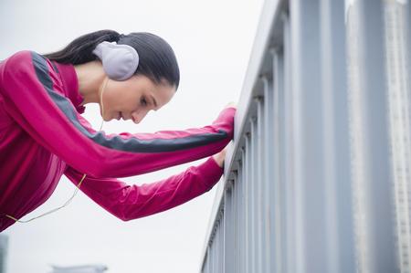 Caucasian woman holding railing, listening to headphones