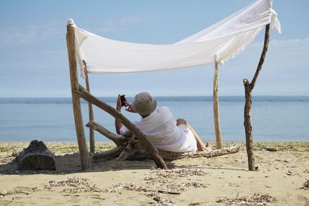 Woman relaxing under homemade shade on beach