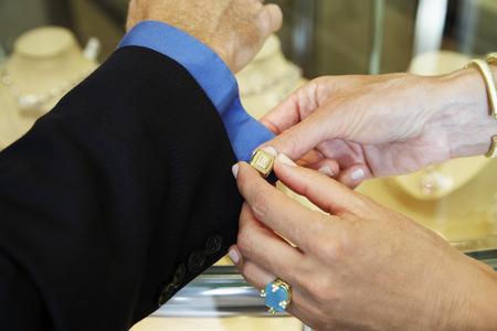 Woman buttoning husbands cuff link
