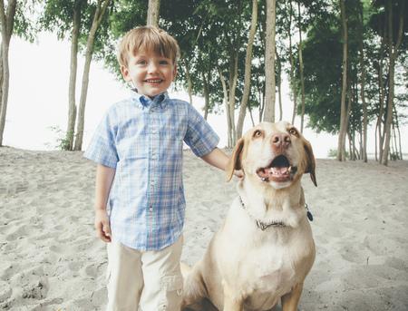 Boy petting dog on wooded beach