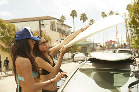 Asian surfers loading boards onto car roof