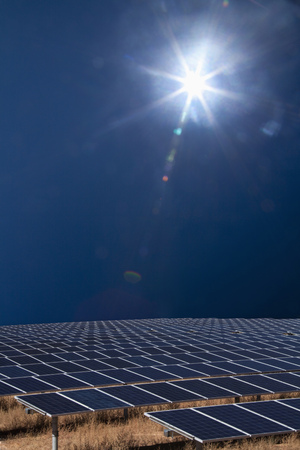 Sun shining over field of solar panels LANG_EVOIMAGES