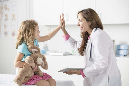Doctor and patient high fiving in office LANG_EVOIMAGES