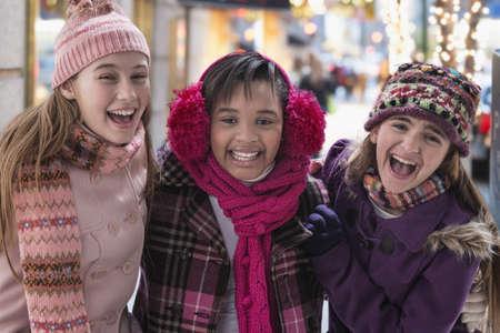 Smiling girls wearing winter coats on city sidewalk LANG_EVOIMAGES