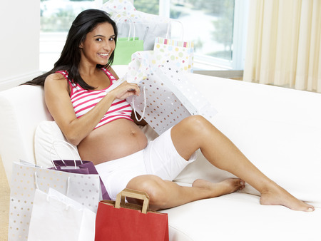 Pregnant Hispanic woman opening gifts