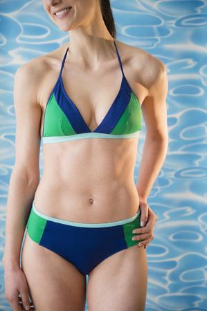 Caucasian woman wearing bikini by pool