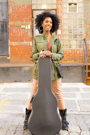 Mixed race woman with guitar case on city street LANG_EVOIMAGES