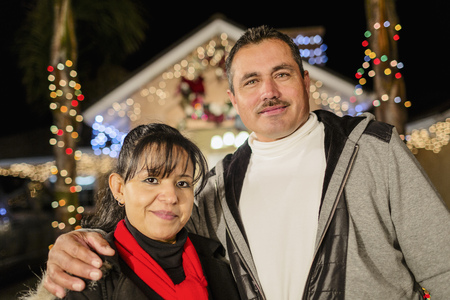 Hispanic couple smiling outside house decorated with string lights LANG_EVOIMAGES