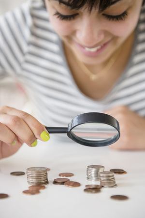Mixed race woman examining stacks of coins with magnifying glass