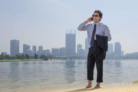 Hispanic businessman talking on cell phone on beach, Perth, Western Australia, Australia