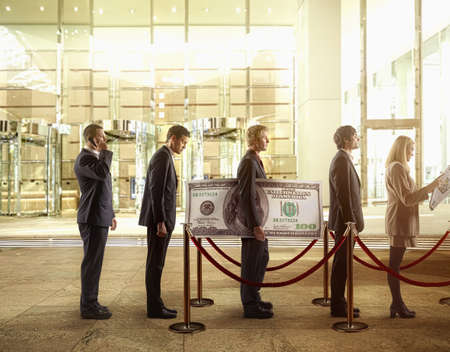 Businessman holding large hundred dollar bill in bank line LANG_EVOIMAGES