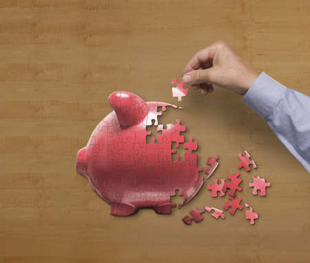 Businessman putting together piggy bank puzzle on desk LANG_EVOIMAGES