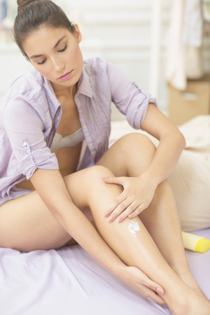 Caucasian woman applying moisturizer to leg LANG_EVOIMAGES