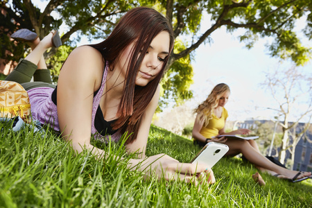 Caucasian girl using cell phone in grass