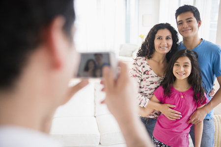 Hispanic family taking cell phone photograph in living room LANG_EVOIMAGES