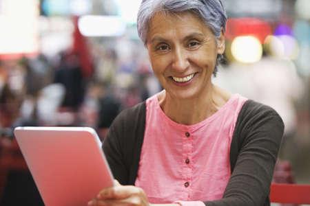 Hispanic woman using tablet computer at cafe