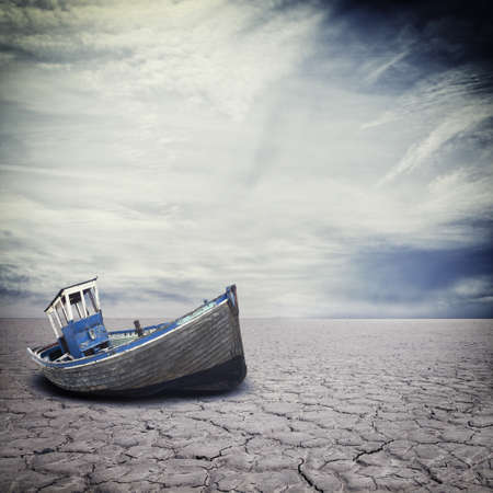 Dilapidated boat on dry cracked river bed LANG_EVOIMAGES