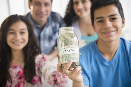Hispanic family holding full vacation savings jar LANG_EVOIMAGES
