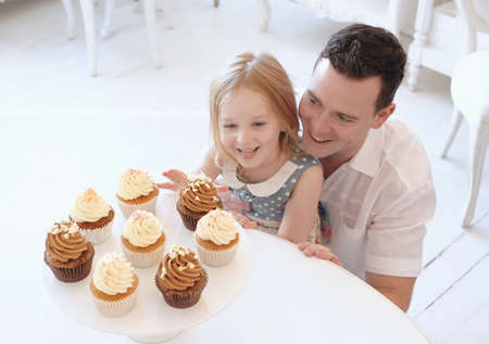 Caucasian father and daughter admiring tray of cupcakes LANG_EVOIMAGES