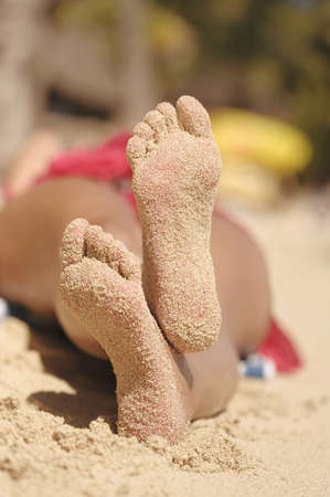 Close up of Hispanic womans sandy feet on beach LANG_EVOIMAGES