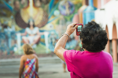 Older woman photographing urban mural