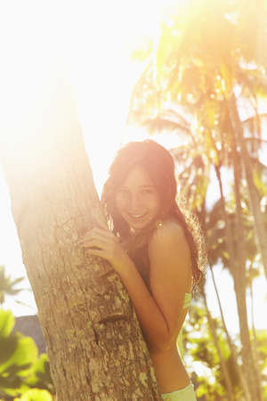 Caucasian girl hugging palm tree