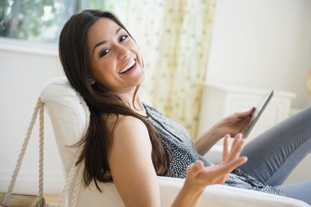 Woman using tablet computer in armchair
