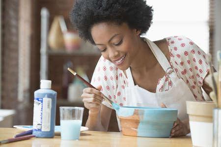African American artist painting pot in studio