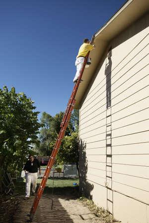 Caucasian men painting house LANG_EVOIMAGES