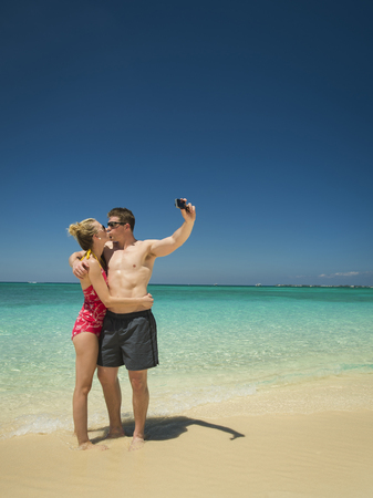 Caucasian couple taking selfie on tropical beach LANG_EVOIMAGES