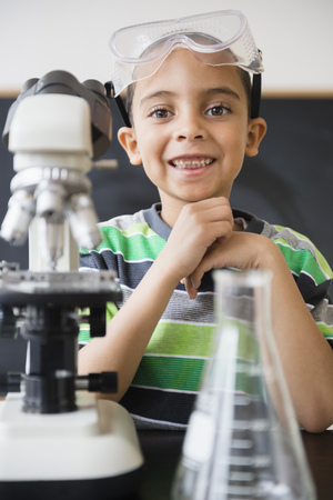 Mixed race boy doing experiments in science class